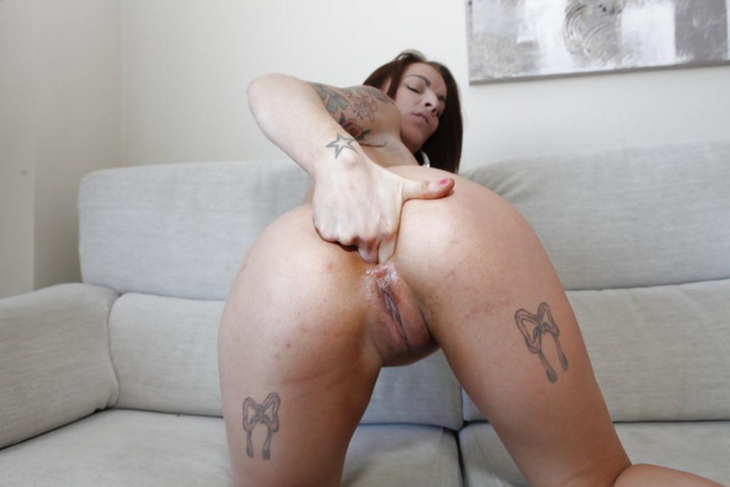 Молодая брюнетка с татуировками на теле показывает стриптиз