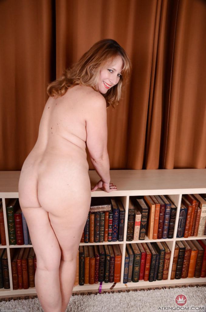 Зрелая женщина лежит на книжной полке и показывает небритую киску