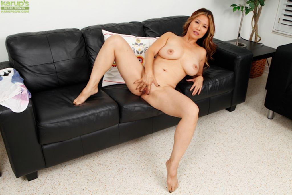 Азиатская женщина занимается мастурбацией на черном диване