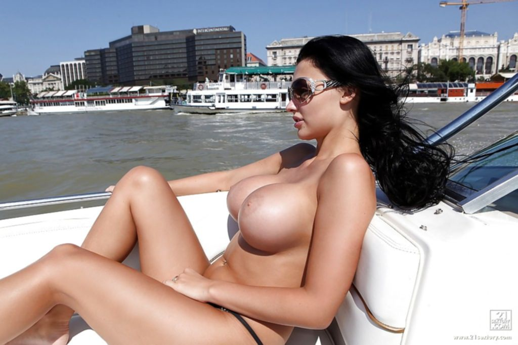 Сисястая брюнека загорает на лодке голая